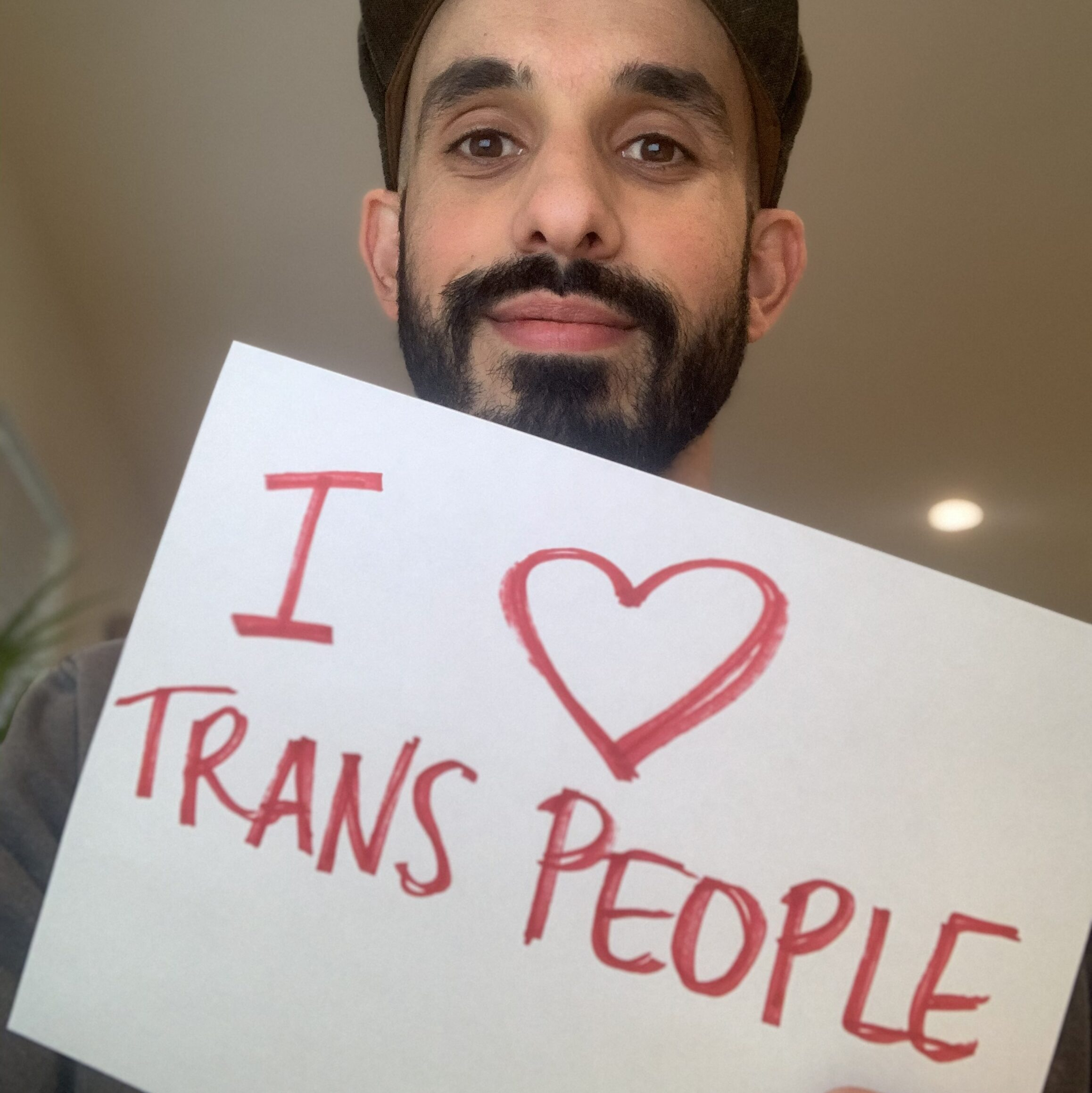 "Eric Garcia, a light-skinned Latinx person with a thick black mustache and beard holds a handwritten sign that says ""I (drawn heart) Trans People"""