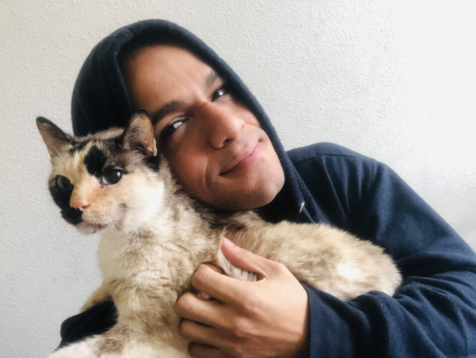 JanpiStar, Light brown queer latinx hugging a Cat called Moxie. JanpiStar is wearing a Navy Blue Hoodie Jacket and Moxie has different spots color; dark brown , yellow and white.
