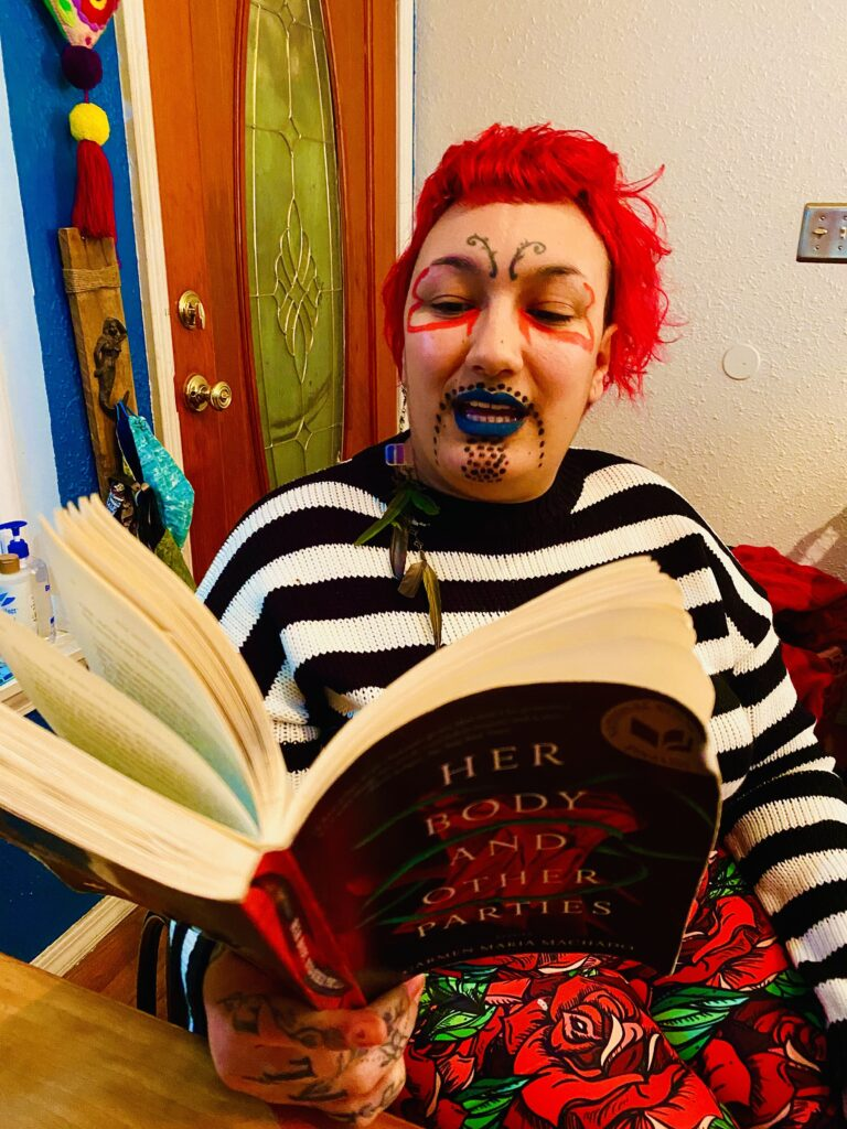 A portrait of NEVE, brown-skinned and bright red-haired, tattooed antenna at his third eye practically trembling, mid-sentence, teal painted lips pulling up to reveal cream-colored teeth, reading aloud from a book called Her Body and Other Parties by Carmen María Machado. NEVE is wearing a black and white horizontally striped sweater, leggings printed with an art deco/mosaic-like graphic of red roses and green leaves, and their face is decorated with petal-shaped lines beneath their eyes and a goatee made of dots.
