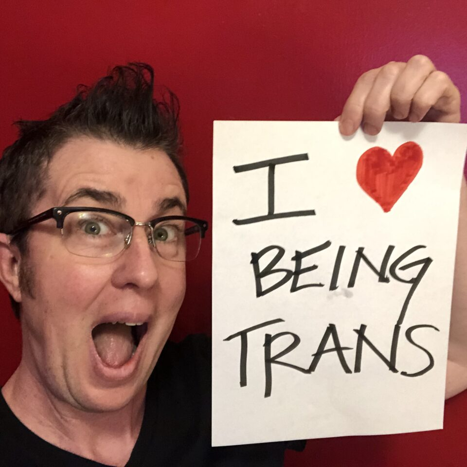 """Sean Dorsey, a white trans masculine person, with short dark brown hair seen from the neck up with a big smile. He holds up a handwritten sign that says """"I (drawn red heart) being trans."""""""