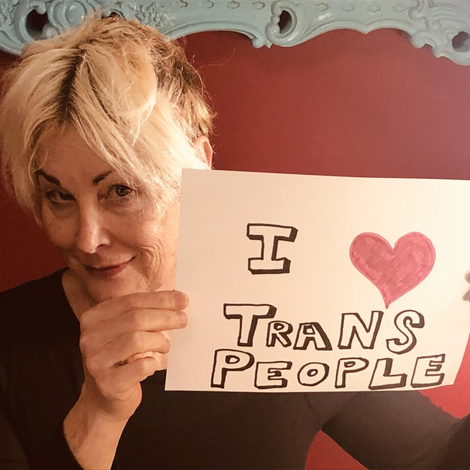 """Shawna Virago, a white person with blond hair smiles and holds up a sign that says """"I (drawn red heart) Trans People"""""""