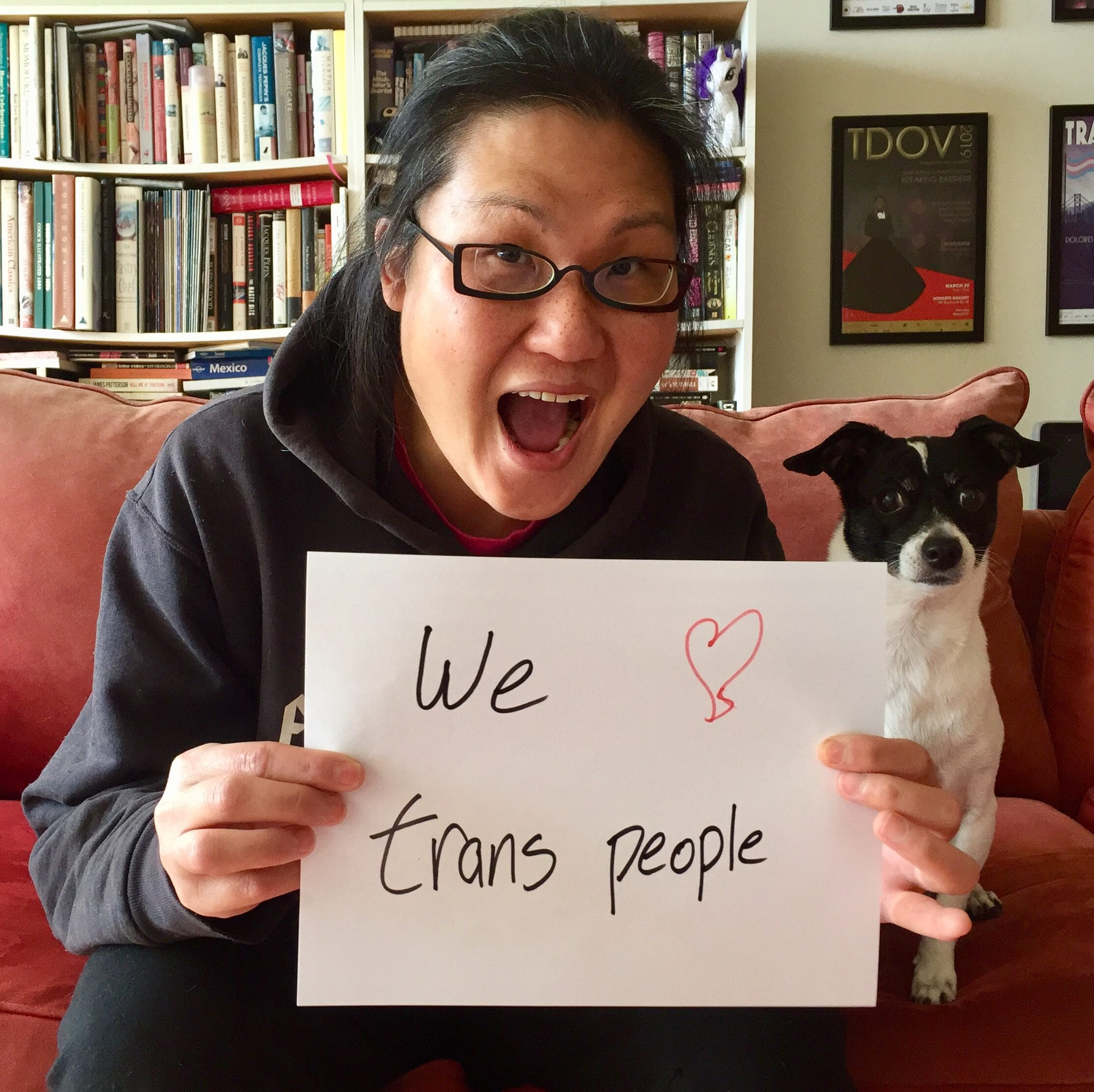 """Gwen Park, a Korean-American trans woman with long black hair sits next to her dog, Slate, a white and black terrier mix. Gwen smiles and holds a handwritten sign up that says """"We (drawn red heart) trans people"""""""