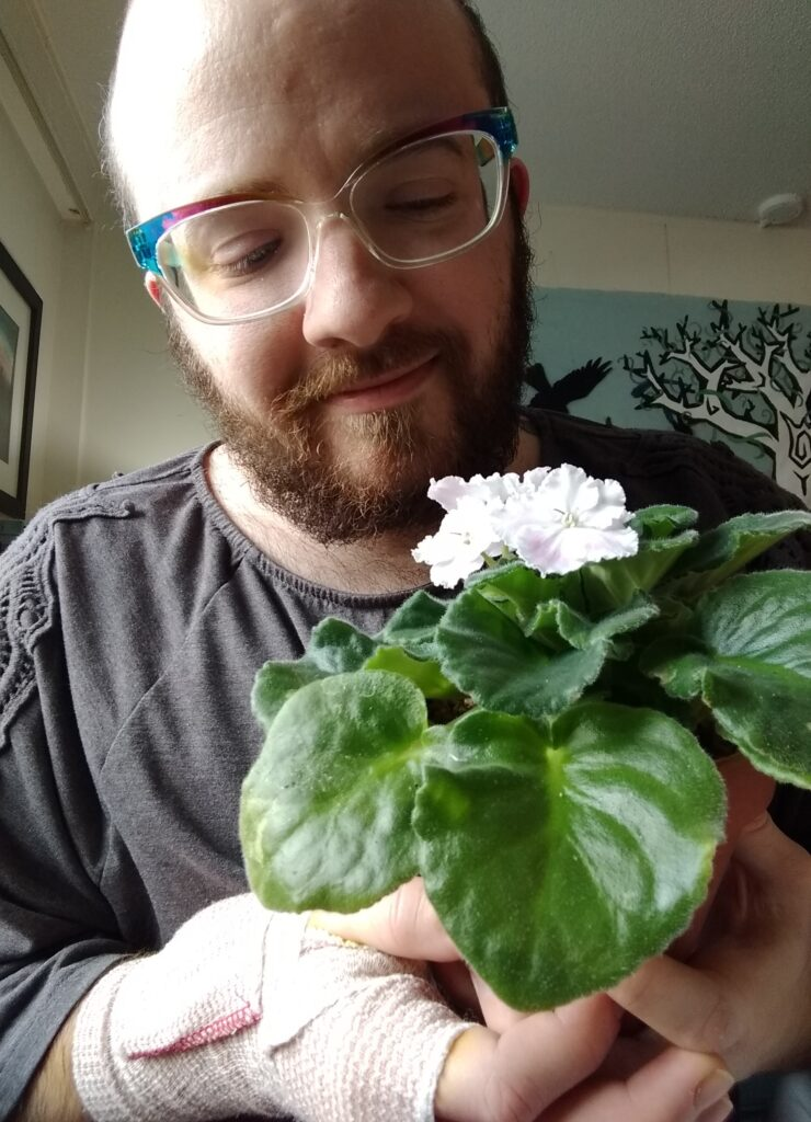 Toby, a white person with a short, dark brown beard and not much hair, looks fondly downward at a potted african violet, with fuzzy green leaves and nearly-white pale purple flowers. One of their hands, cradling the pot, is compression wrapped.